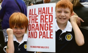 two red haired kids holding a sign that says all hail the red orange and pale